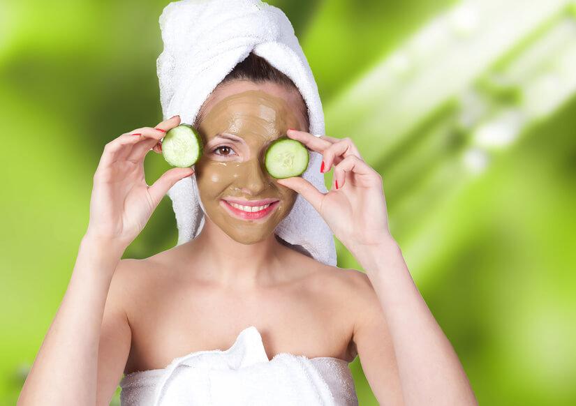 Frau mit Gesichtsmaske aus Heilerdehält sich Gurkenscheiben vor die Augen
